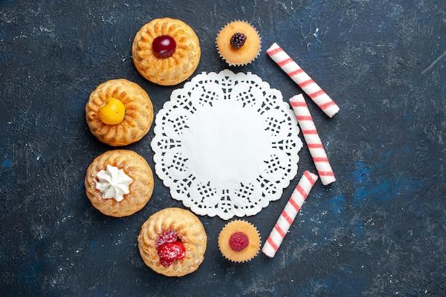 Vista de cima pequenos bolos deliciosos junto com balas rosa na mesa escura bolo de biscoitos doce de frutas