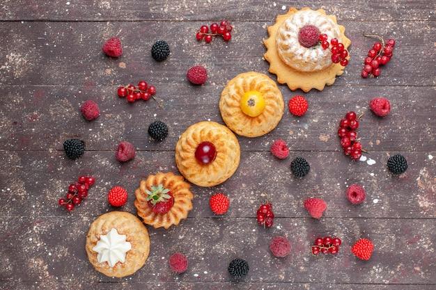 Vista de cima pequenos bolos e biscoitos deliciosos com frutas diferentes ao longo de todo o fundo marrom.