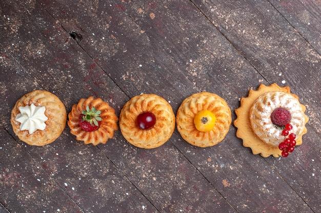 Vista de cima pequenos bolos e biscoitos deliciosos com frutas forradas no fundo marrom.