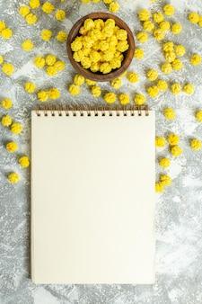 Vista de cima, pequenos doces amarelos com bloco de notas na superfície branca.