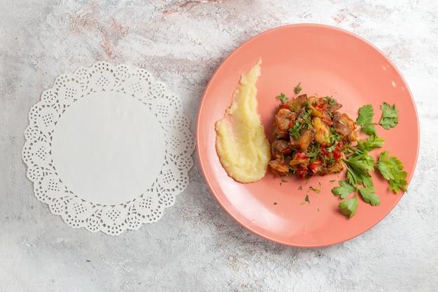 Vista de cima pequenos pedaços de carne cozida com purê de batatas e verduras na superfície branca
