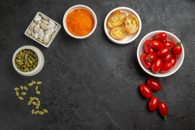 Vista de cima pequenos tomates frescos com sementes e abóbora em forma de cogumelo na cor madura de sementes de fundo cinza