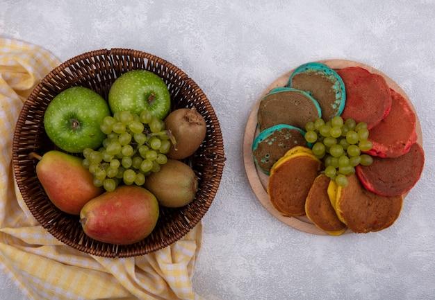 Vista de cima peras com maçãs verdes, uvas e kiwi em uma cesta em uma toalha amarela quadriculada com panquecas coloridas em um suporte sobre um fundo branco
