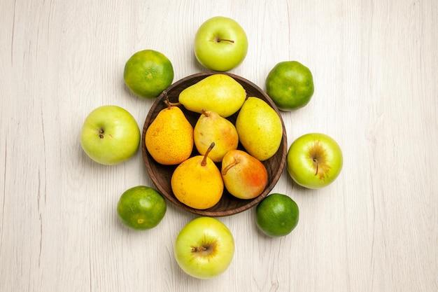 Vista de cima peras frescas maduras frutas doces com maçãs e tangerinas na mesa branca frutas amarelas frescas maduras