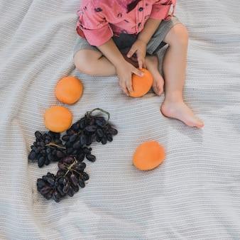 Vista de cima. pés de menino. segurando uma laranja brilhante nas mãos. senta-se em uma colcha branca