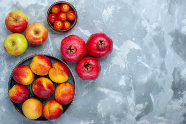 Vista de cima, pêssegos frescos, deliciosas frutas de verão com maçãs em uma mesa branca clara