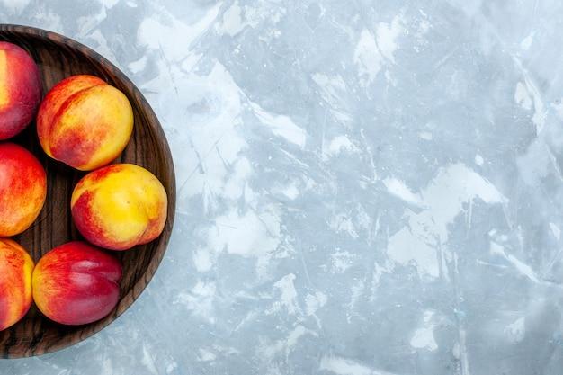 Vista de cima pêssegos frescos e frutas saborosas em um prato marrom sobre a mesa branca clara