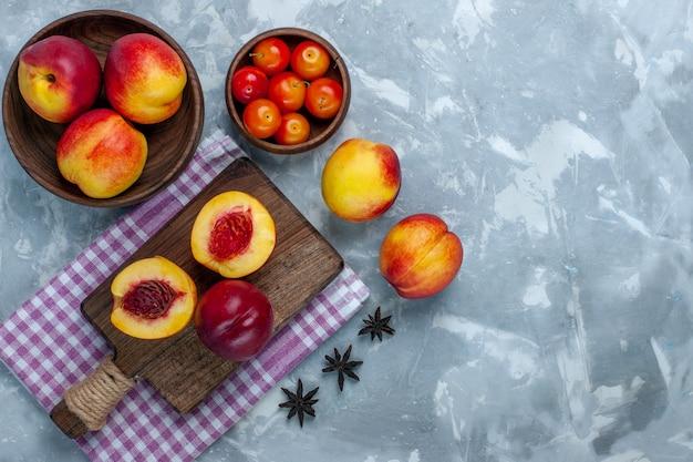Vista de cima pêssegos frescos frutos maduros e saborosos dentro do prato marrom na superfície branca clara