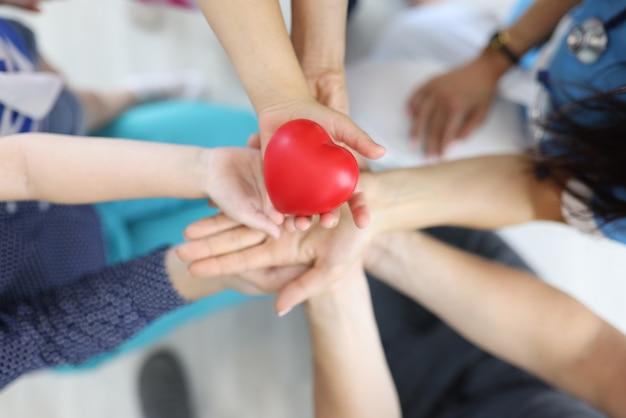 Vista de cima pessoas segurando um coração vermelho