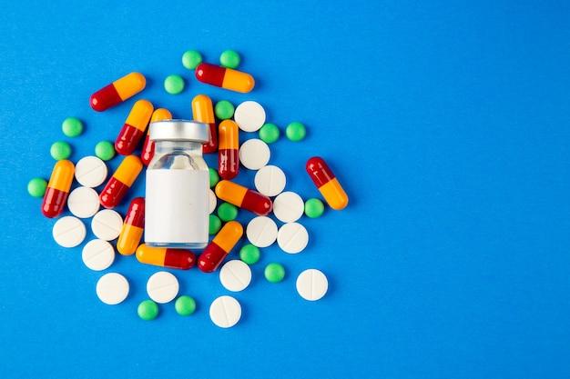 Vista de cima pílulas diferentes com vacina em fundo azul