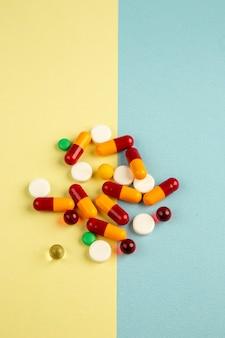 Vista de cima pílulas diferentes em fundo azul amarelo