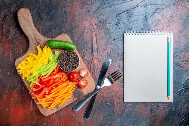 Vista de cima pimentão colorido cortado pimenta preta tomate pepino na tábua de cortar lápis no garfo do caderno e faca na mesa vermelho escuro