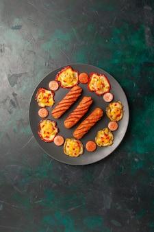 Vista de cima pimentão cozido com linguiça frita dentro do prato na superfície verde escura