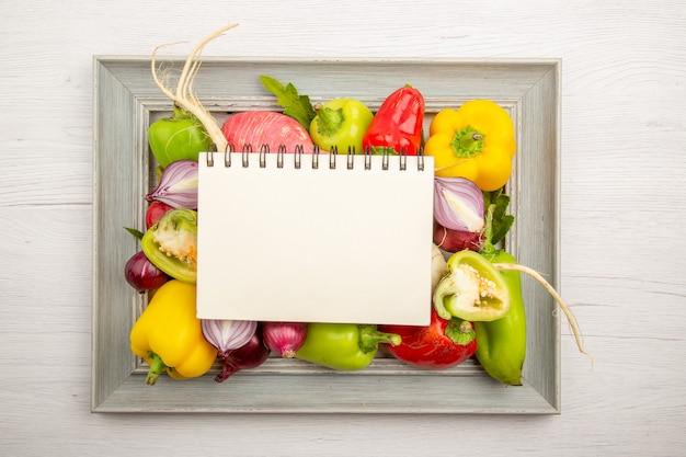 Vista de cima pimentão fresco com rabanete e cebola na mesa branca refeição de vegetais cor pimenta salada madura foto de vida saudável