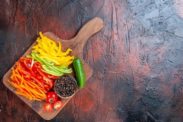 Vista de cima pimentas cortadas coloridas pimenta preta tomates pepino em uma tábua no espaço livre da mesa vermelho escuro