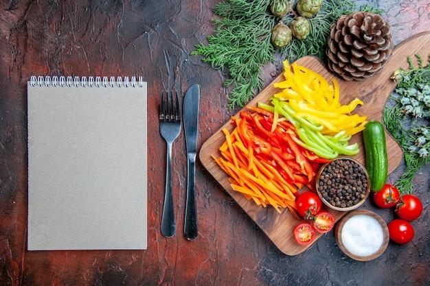 Vista de cima pimentas cortadas coloridas pimenta preta tomates pepino na tábua de cortar caderno faca de sal e garfo na mesa vermelha escura
