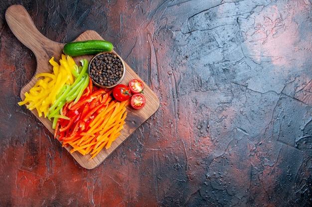 Vista de cima pimentas cortadas coloridas pimenta preta tomates pepino na tábua de cortar espaço livre na mesa vermelha escura