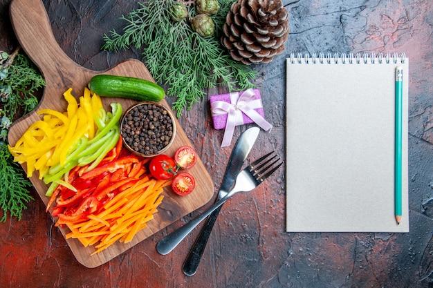 Vista de cima pimentas cortadas coloridas pimenta preta tomates pepino na tábua de cortar lápis no bloco de notas garfo e faca pequeno presente na mesa vermelho escuro
