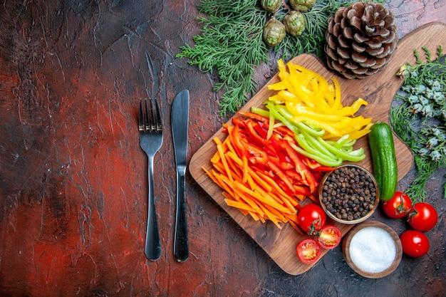 Vista de cima pimentas cortadas coloridas pimenta preta tomates pepino na tábua de corte garfo e faca ramos de pinheiro sal na mesa vermelha escura espaço livre