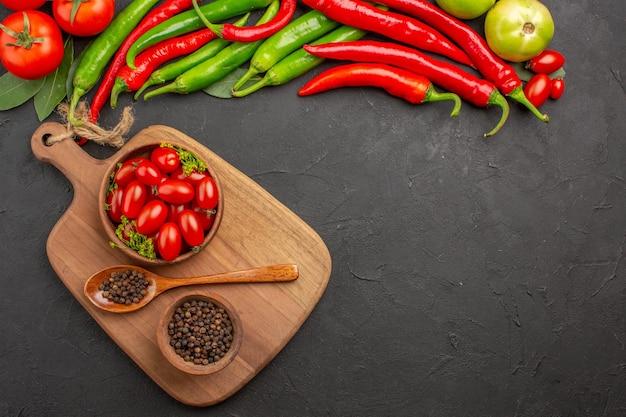 Vista de cima pimentas vermelhas e verdes quentes e tomates com folhas de louro tigelas com tomates cereja e pimenta preta e colher em uma tábua de cortar em solo preto com espaço livre