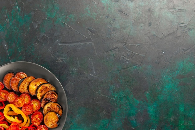 Vista de cima pimentões cozidos com berinjelas na superfície verde escura