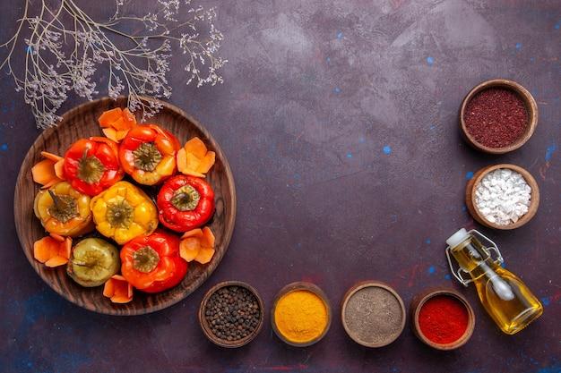 Vista de cima pimentões cozidos com carne moída e diferentes temperos em comida de carne bovina vegetal e de superfície escura