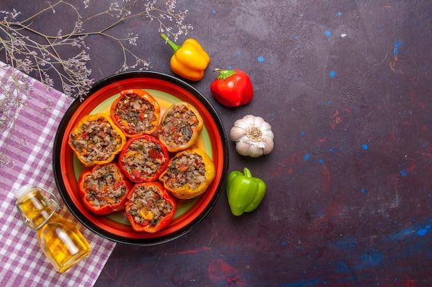 Vista de cima pimentões cozidos com carne moída e óleo em uma mesa escura refeição vegetais comida carne dolma