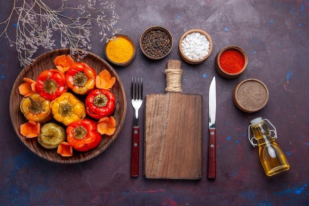 Vista de cima pimentões cozidos com carne moída e temperos na mesa escura.