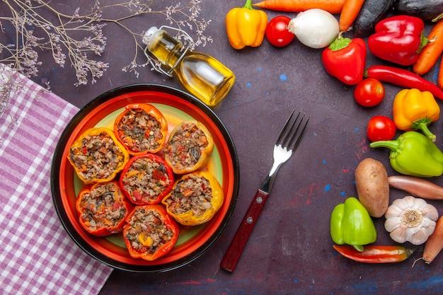 Vista de cima pimentões cozidos com carne moída e vegetais frescos na superfície escura refeição vegetais alimentos carne dolma