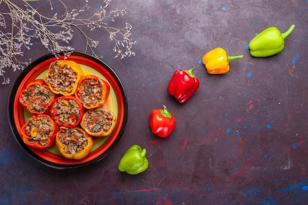 Vista de cima pimentões cozidos com carne moída em uma mesa cinza refeição carne dolma comida vegetais carne
