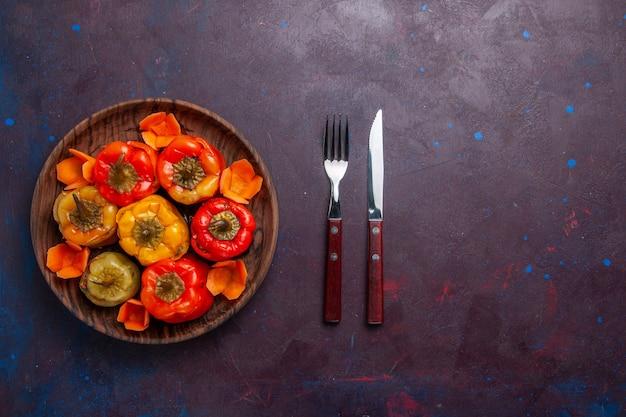 Vista de cima pimentões cozidos com carne moída por dentro em fundo cinza escuro refeição comida carne vegetal cozinhar