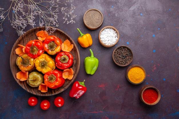 Vista de cima pimentões cozidos com temperos de carne moída em uma refeição de superfície cinza-escura com carne vegetal
