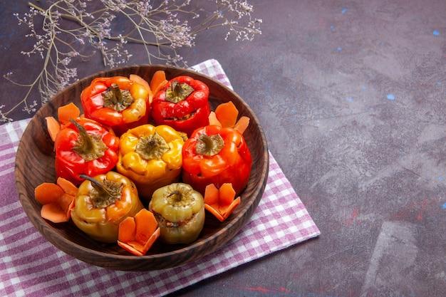 Vista de cima pimentões cozidos com temperos diferentes em mesa cinza comida carne dolma vegetal