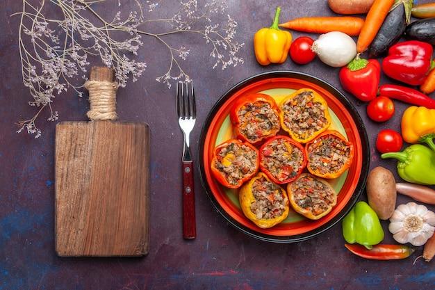 Vista de cima pimentões cozidos com vegetais e diferentes temperos em uma superfície cinza escura comida dolma refeição vegetal carne