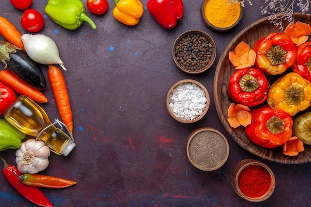 Vista de cima pimentões cozidos com vegetais frescos e temperos em uma refeição de superfície cinza comida dolma carne bovina vegetal