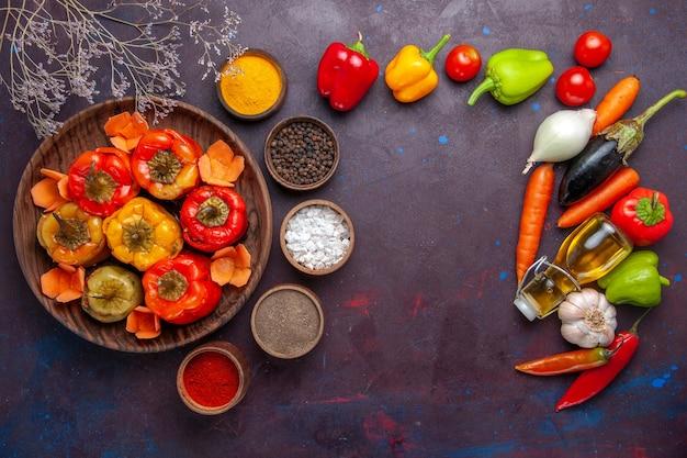 Vista de cima pimentões cozidos com vegetais frescos e temperos em uma refeição de superfície cinza dolma comida vegetais carne bovina