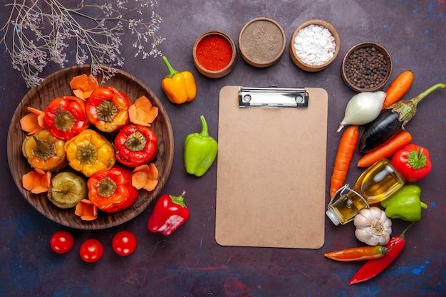 Vista de cima pimentões cozidos com vegetais frescos e temperos em uma refeição de superfície cinza escura vegetais dolma carne bovina