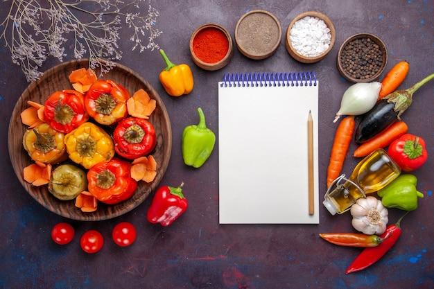 Vista de cima pimentões cozidos com vegetais frescos e temperos na mesa cinza refeição vegetais dolma carne bovina