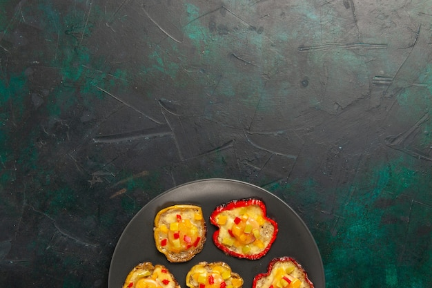 Vista de cima pimentões cozidos para o almoço dentro do prato em superfície verde-escura