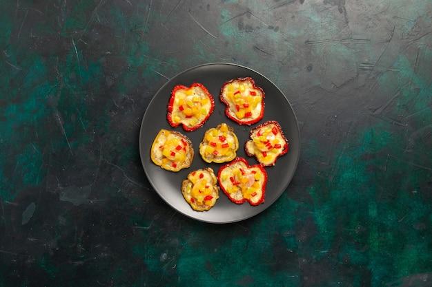 Vista de cima pimentões cozidos para o almoço dentro do prato na superfície escura