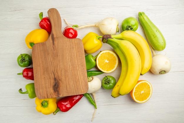 Vista de cima pimentões frescos com bananas e laranja na mesa branca, salada, vida saudável, foto, cor madura, dieta