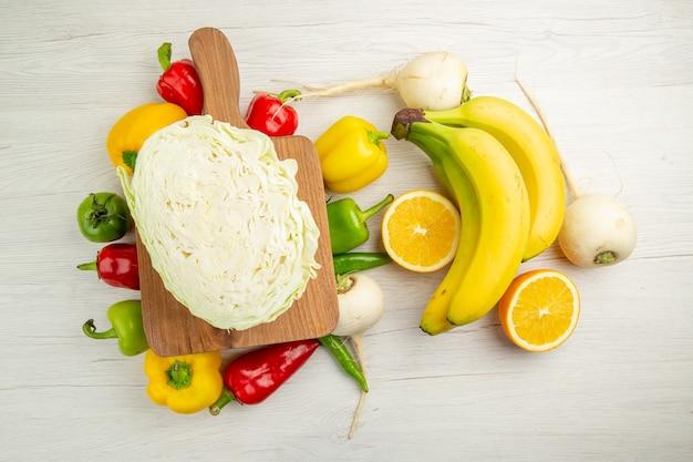 Vista de cima pimentões frescos com bananas e laranja no fundo branco salada vida saudável foto cor madura dieta