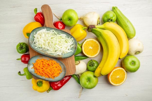 Vista de cima pimentões frescos com bananas, maçãs e laranja no fundo branco salada, vida saudável, fotos, vida saudável, dieta de cor madura