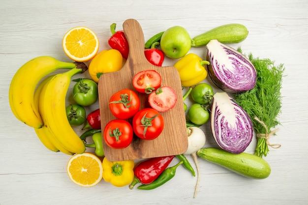 Vista de cima pimentões frescos com bananas, tomates e repolho roxo no fundo branco cor dieta madura vida saudável salada foto