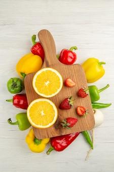 Vista de cima pimentões frescos com fatias de laranja e morangos no fundo branco salada foto colorida madura dieta saudável