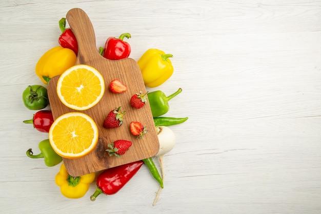 Vista de cima pimentões frescos com fatias de laranja em fundo branco salada foto colorida vida saudável dieta saudável espaço livre