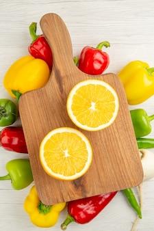 Vista de cima pimentões frescos com fatias de laranja em uma salada de fundo branco foto colorida madura dieta saudável
