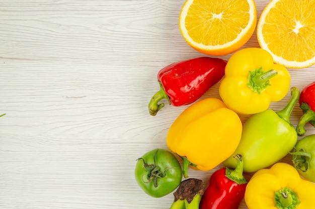 Vista de cima pimentões frescos com laranjas em um fundo branco foto madura salada de farinha de frutas cor madura
