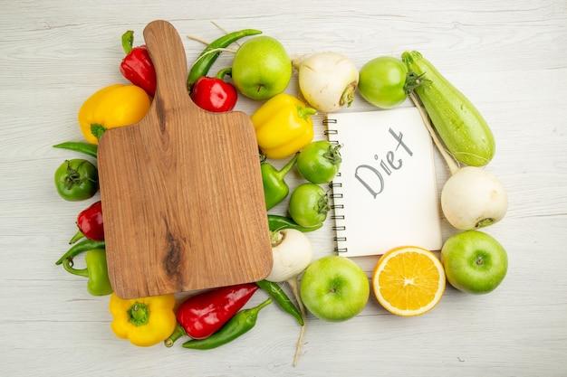 Vista de cima pimentões frescos com maçãs e laranjas no fundo branco foto colorida salada vida saudável dieta madura
