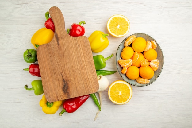 Vista de cima pimentões frescos com tangerinas na mesa branca salada dieta foto colorida madura vida saudável